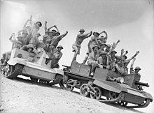 Soldiers standing on two mechanised vehicles in the desert