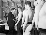 A Royal Navy surgeon lieutenant examining sailors who have come aboard HMS RODNEY, October 1940. A1219.jpg