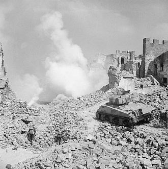 Military history of New Zealand during World War II - A Sherman tank of 19th Armoured Regiment, 4th New Zealand Armoured Brigade supporting infantry of 6th NZ Infantry Brigade, in a reconstruction of the action at Cassino, Italy, 8 April 1944.