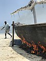 A man sets fire and coats a boat on the beaches of Zanzibar.jpg
