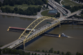 Aerial view of Pittsburgh, Pennsylvania, with a focus on a tugboat and barge passing under the Fort Pitt Bridge, a steel, double-decked bowstring arch bridge that spans the Monongahela River near its confluence with the A (highsm.58444).png
