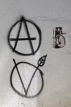 Fotografía de un grafiti del círculo A y del círculo V en la pared