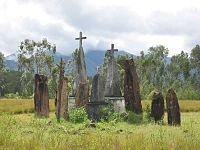 Half a dozen upright rough hewn stones about four feet high, some topped with stone crosses
