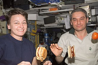 Astronauts making and eating hamburgers on board the ISS, August 2007 AstronautsEatingBurgers.jpg