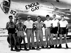 "A Silver aircraft with ""Enola Gay"" and ""82"" painted on the nose. Seven men stand in front of it. Four are wearing shorts, four are wearing T-shirts, and the only ones with hats have baseball caps. Tibbets is distinctively wearing correct uniform."