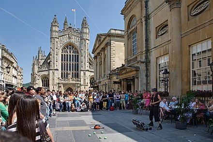 Bath is popular with tourists all year round. An entertainer is performing in front of Bath Abbey; the Roman Baths are to the right. Bath Abbey and Entertainer - July 2006.jpg