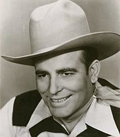 A smiling man wearing a cowboy hat and neckerchief