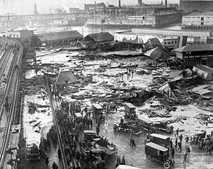 Smashed buildings and detritus litter a flooded street following the Boston Molasses Disaster of 1919.
