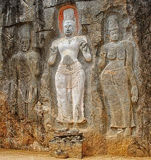 Buduruvagala - Avalokitesvara (the bodhisattva of compassion). To the left of this white-painted figure is a female figure thought to be his consort, Tara. Local legend says the third figure represents Prince Sudhana.