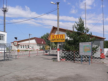"Three small buildings beside a road. The road is blocked with a white and red striped gate and a yellow and red sign reads ""KPP Dityatki"" in Ukrainian"