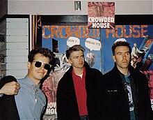 Drei Männer stehen vor Plakaten für die Band.  Der Mann links trägt eine Sonnenbrille, lächelt und passt seine dunkle Jacke an.  Der Mann in der Mitte starrt nach links und trägt eine ähnliche dunkle Jacke.  Der dritte Mann starrt ebenfalls zu seiner Linken und hat eine dunkle Jacke.