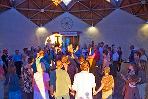 Dances of Universal Peace - A 'Dances of Universal Peace ' session with the dance teacher and accompanying musicians in the centre and the dancers of all ages and abilities in circles around them.