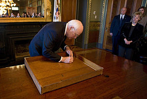Theodore Roosevelt desk -  Vice-President Cheney signing the desk drawer near the end of his term in office, January 12, 2009.