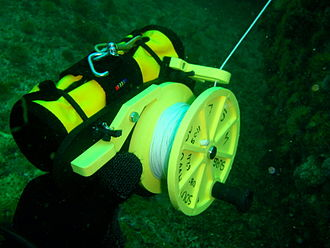 Distance line - Plastic general purpose ratchet dive reel with rolled up DSMB attached with bungee loops.
