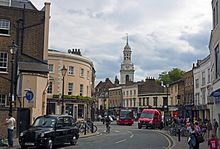 A curving street with older two- and three-storey buildings on either side. In front is a black London taxicab with an advert; midway down the street is an intersection with heavy traffic. A cupolaed clock tower rises in the rear
