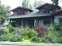 Photograph of a Craftsman bungalow with larger dormers, porch, and fieldstone steps.