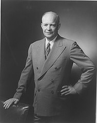 Dwight D. Eisenhower, three-quarter length portrait, standing, facing slightly left, hand on back of chair.jpg
