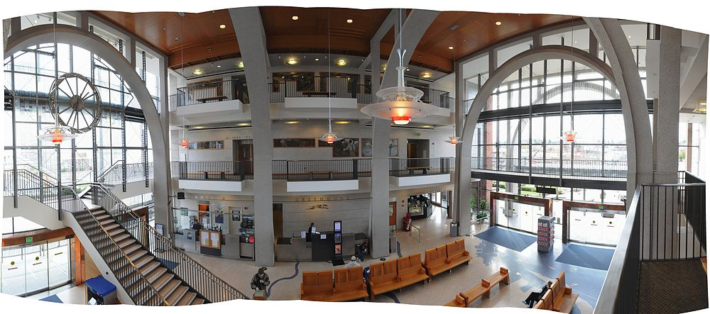 The lobby of a large building, with balconies from two upper stories framed by large steel arches.