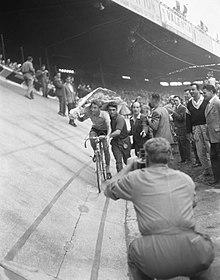 Photographie en noir et blanc d'un cycliste sur son vélo brandissant un bouquet de fleurs et poussé par un spectateur.