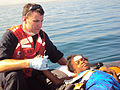 Flickr - DVIDSHUB - U.S. Coast Guard Member Gives Aid to Haitian Refugee.jpg