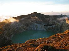 A photograph depicting a blue sky with white clouds at the top, a grey mountain range in the middle, a blue body of water below that, and a rocky terrain in the foreground.