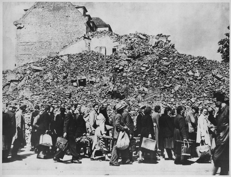 File:Germany. (A line of people with baggage in front of a pile of building rubble.) - NARA - 541694.tif