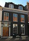 foto van Huis met gepleisterde lijstgevel met composiete kapitelen dragende pilasters ter weerszijden van de deur en schuiframen