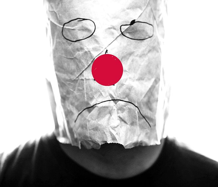 File:Gray paper bag with sad smiley over head with red nose.jpg