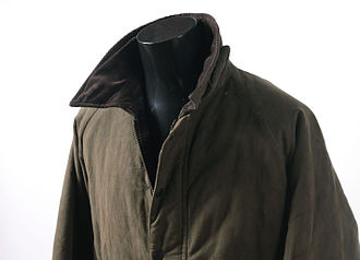 British country clothing - A men's green waxed jacket with brown corduroy collar.