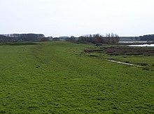 field with raised grass track leading to distant mound