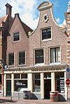 foto van Huis met eenvoudige ingezwenkte halsgevel met fronton, 1723 gedateerd. Kerkplein 40 is beschermd, 41 niet.
