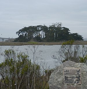 Indian Island (Humboldt Bay) - National Register of Historic Places marker on Woodley Island in foreground, Indian Island on other side of channel.