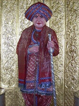 Jalaram Bapa - Jalaram Bapa idol at a temple in Vadodara, dressed in colorful attire on occasion of Jalaram Jayanti holding a danda and wearing a turban.