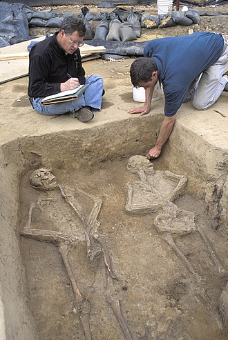 Douglas W. Owsley - Owsley (left) and Historic Jamestowne archaeologist, Danny Schmidt, discussing the double burial of two European males at the James Fort site