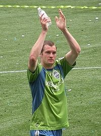 the head and torso of a young man, wearing a green and blue top and blue shorts, standing on a grass field. He has his arms raised above his head in what appears to be a clapping motion.