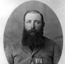 A black and white head and shoulders photograph of a balding white man with a full, dark, beard and a heavy wool coat