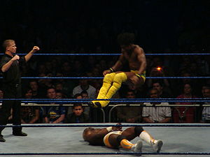 Leg drop - Kofi Kingston performing the double leg drop on Shelton Benjamin