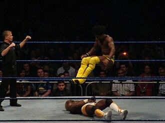 Leg drop - Kofi Kingston performing the double leg drop on Shelton Benjamin