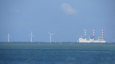 Wind turbines of the Mampuri and Madurankuliya wind farms next to the Lakvijaya Power Station, as seen from the Puttalam Lagoon.