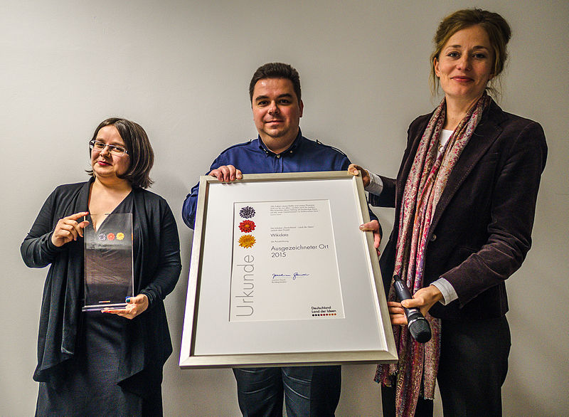 Photograph of Magnus Manske in October 2015, accompanied by two women, holding up a large framed award