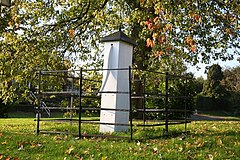 White painted village pump within wrought iron fence, under an autumnal maple, with shed leaves on the surrounding grass.