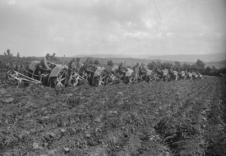 Line of tractors ploughing (4520565207)