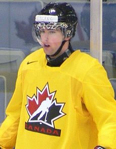 Young male ice hockey player in full gear stopped during a practice.