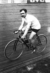 A black-and-white photograph of a man with three-colored sweater and shorts with a moustache sitting on a bicycle.