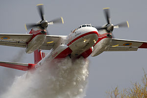 Antonov An-32 - A State Emergency Service of Ukraine An-32 firefighting aircraft dumps water on a forest fire.