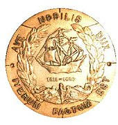 "A round brass metal object features a sailing ship in the center over the U.S. Navy submarine service chest insignia of a dolphin and framed in a laurel wreath. In a circle around the edges are the Latin words ""Ave Nobilis Dux, Iterum Factum Est"" which translates to ""Hail Noble Captain, It is Done Again."""