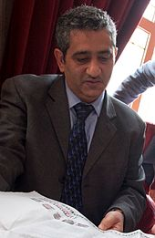 A man wearing a suit with short black and white hair, Mansoor Al-Jamri, reading a paper