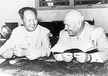 En skallet mann og en yngre kineser sitter og smiler, den skallede mannen holder en vifte