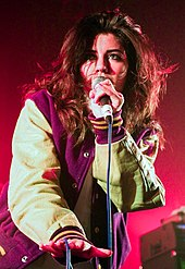 A young brunette woman wearing a baseball-style jacket, singing into a microphone against a pinkish background.