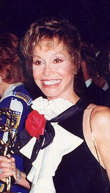 A smiling women wearing a black and white dress holds a golden statuette.